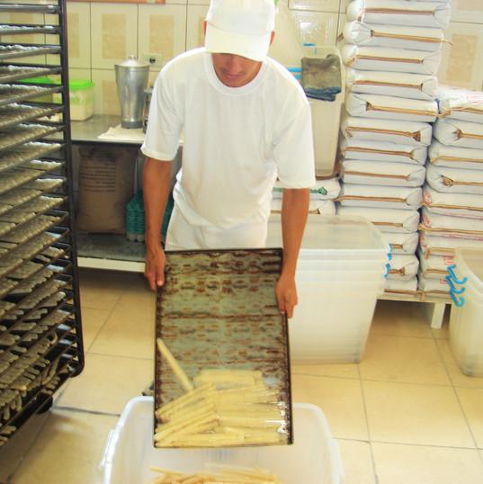 Colaborador descarrega os biscoitos assados para serem embalados