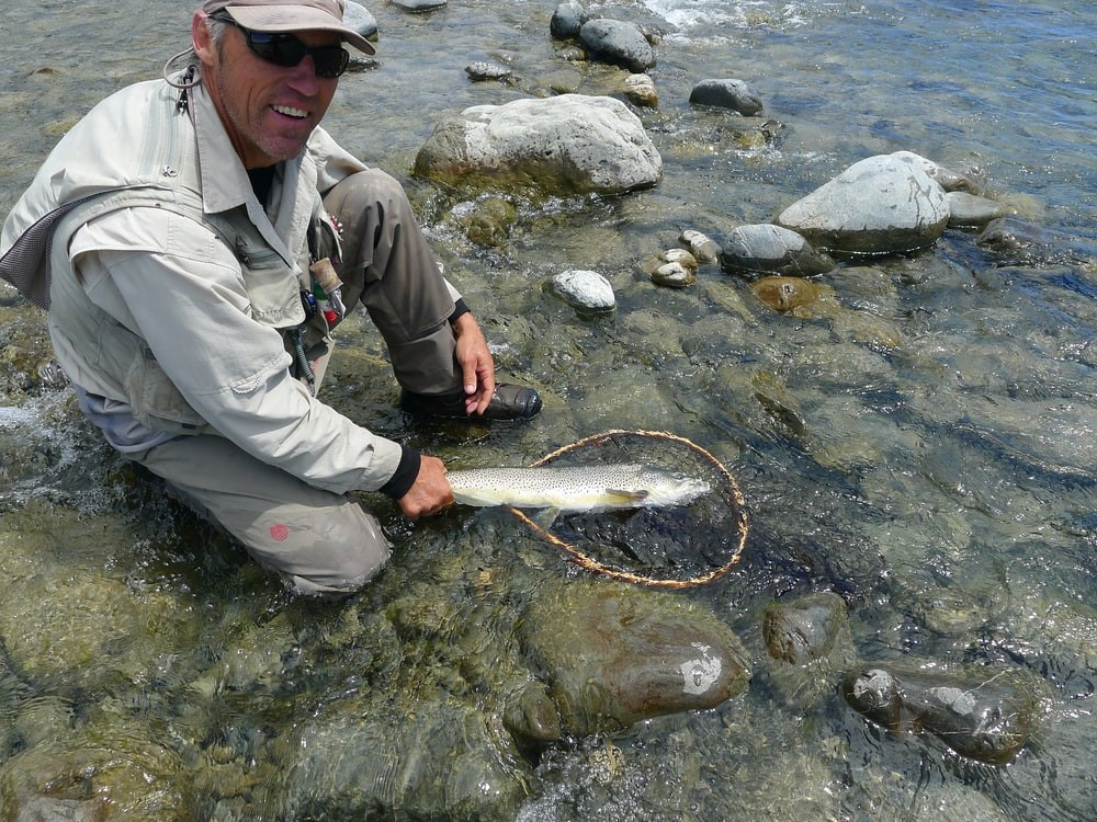 A man posing with a speckled trout in his hand.