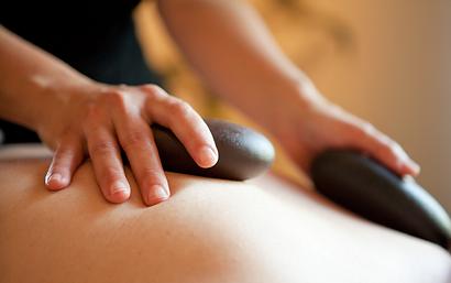 A woman receiving a hot stone massage