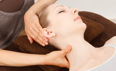 A woman having her neck and shoulders massaged