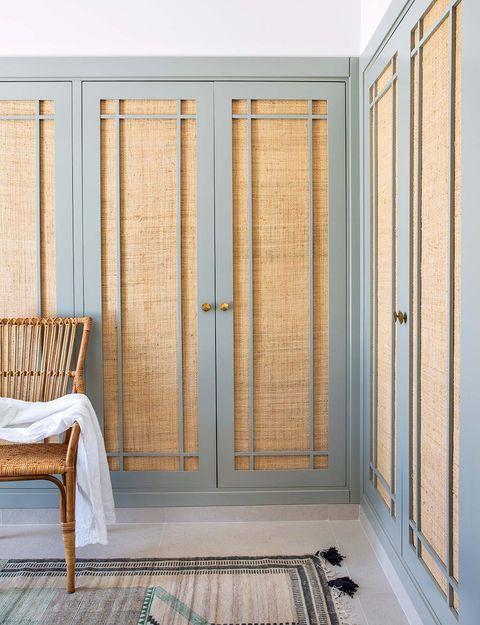 el vestidor para el que se han diseñado armarios lacados en verde con puertas de rafia