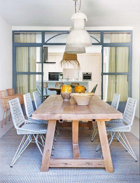 vista de la mesa de madera del comedor, con la cocina al fondo