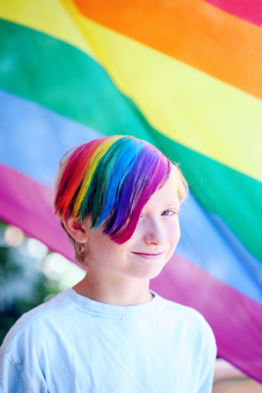 rainbow hair on Saint Paul child standing in front of a rainbow flag