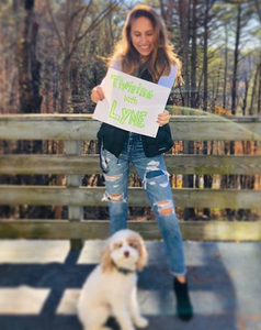 "girl standing behind white dog with sign that reads ""thriving with lyme disease"""