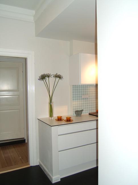 For at gøre køkkenet visuelt større og entréen lysere er dele af væggen ned imellem de to rum bækkes ned. Halvmuren er gavlen på køkkenet og loftet sænket, så køkkenet fremstår som en niche. Det er blevet visuelt og funktionelt større - og åbner sig op mod entreen.