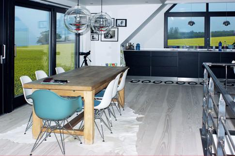 Køkken/alrummet har en fantastisk udsigt!!! En stor kvist med gulv-loft vinduer giver ståhøjde udover skunk-linjen og øger etagearealet. Et moderne køkken - med mørkebrune trælåger og sorte greb passer godt huset 70'er stil. Højskabene er bygget ind i skunken og optager ikke noget unødvendig plads. Alt ialt er de 180 m2 udnyttet superoptimalt og de 6 beboere har fået masser af plads.