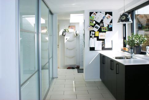Bryggers-delen med teknik og vaskemaskine er blevet skjult bag store skydelåger, og rummet kan derved finde sin anden anvendelighed som fællesrum for børnene.