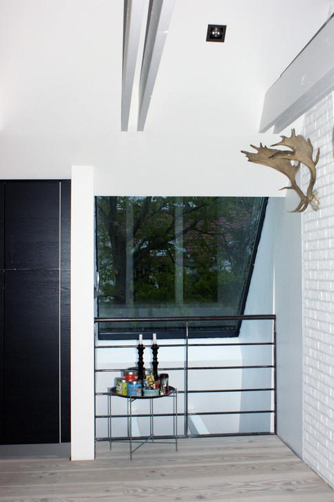 Indgangspartiet er blevet trukket frem i facaden og det har givet en større entré med indbygget garderobe. Entré-rummet er dobbelthøjt og åbner sig mod køkken/alrummet på 1. sal.