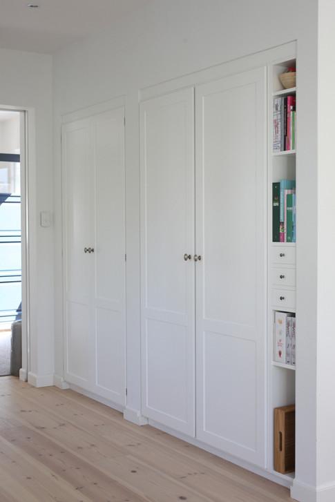 Fra køkkenet er der direkte adgang til et viktualierum. Åbningen hertil er speciallavede højskabslåger i samme udtryk som de øvrige de låger, således det lignede et indbygget skab. I nichen ved siden af er et højskab og en smal reol indbygget. Samlet set et funktionelt og smukt køkken med enkle fine linjer.