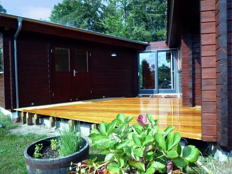 Birgit og Ole køber et sommerhus på Norddjurs, tæt ved Bønnerup Strand. De har været så heldige at erhverve sig en bjælkehytte, beliggende uforstyrret i en gryde, omgivet af høje træer og beplantede høje. Bjælkehytten rummer en lille stue med køkken, soveværelse, badeværelse, en meget lille entré på godt en kvadratmeter samt et eksternt anneks. Birgit og Ole ser med det samme potentiale i stedet som et familie-samlingssted og meget hurtigt bliver det planen at bygge til. De ønsker endnu en et værelse med to sovepladser samt en større entré og terrasse. Opgaven består i placere endnu en bjælkehytte på grunden (et nye værelse) og tegne bindeleddet imellem den eksisterende bjælkehytte og den nye.