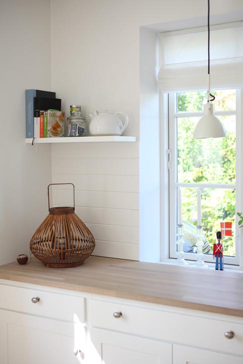 Resultatet er blevet en fyldningslåge i knækket hvid og bordplade i eg. Køkkenmodulerne er blevet indrettet, så det matcher budgettet - dvs at udvalgte skabe har fået faste hylder, som er den billigste løsning.