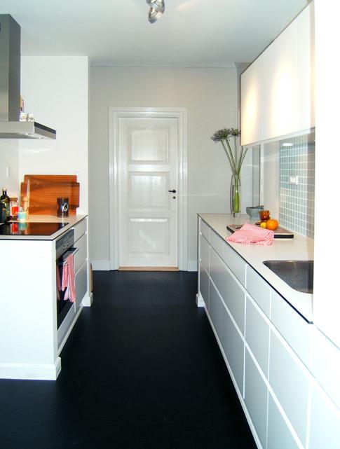 Det moderne køkken er holdt i enkle linjer og er integreret i den gamle herskabslejlighed. Dette ses blandt andet ved at fodpanelet flugter halvmuren så køkkenet synes indbygget. En anden finesse er gulvet. Ens gulv i køkken og entré får rummene til at føles større end de er.