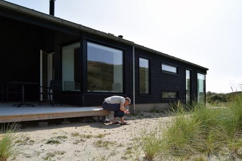 Sommerhuset og carporten placerer sig således at det skærmer for vinden på terrassen. Facaderne, sortmalet bræddebeklædning, vinkler sig lodret og vandret for at få spil i facaden.