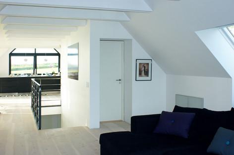 Trappen leder fra entreen mod stuen og et flot kig ud af det store sydvendte vindue i gavlen. Lofter er fritlagte til kip og med synlige bjælker. En ny gæstetoiletkerne opdeler - sammen med trappen - det store rum i stue og køkken/alrum.