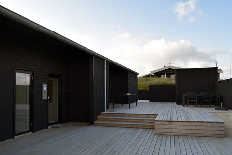 Mange af ideerne fra det oprindelige projekt er så vidt muligt blevet integreret i det nye sommerhus - samt etablering af et stort terrasse-opholdsområde med direkte adgang til sauna og udebruser.