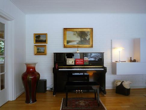 Vægge og loft er blevet malet hvide og endevæggen fik en antikblå farve, dels for at samle det lange rum visuelt, dels for at fremhæve den murede brændeovn som et smukt monument. Desuden rammer den blå nuancer farver i malerier og tæpper, og får øjet til at falde til ro. De mange sofaer og lænestole er blevet udskiftet med en stor, fritstående hjørnesofa i lys beige/mørkeblå nistret stof.