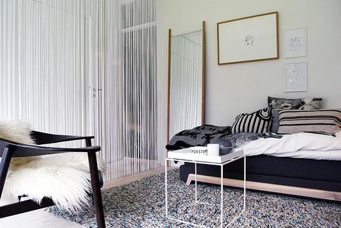 Det største værelse, udover stuen, er både ungdomsværelse - og garderobe for hele familien. Et gennemsigtigt trådgardin skaber en let afgrænsning mellem værelse og garderobe, og giver samtidig rummet intimitet og hygge. Farver og materialer er generelt afstemt i neutrale, nordiske toner på vægge, gulv og i inventar: grå, sort, hvide farver samt egetræ.