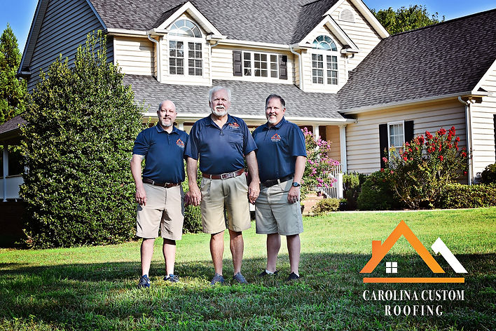 3 smiling men standing on the front lawn of a 2-story tan home with new Carolina Custom Roofing architectual asphalt shingles