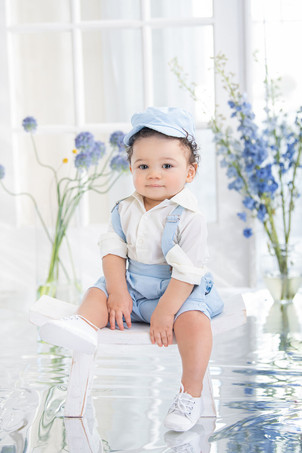 Toddler boy sitting on a white stool bench wearing a matching blue hat and suspender overalls outfit