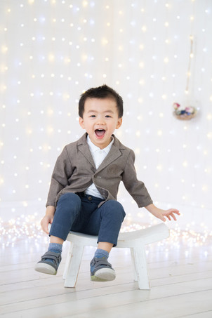 Happy asian toddler boy in photography studio sitting on a white stool bench wearing a casual blazer with denim pants