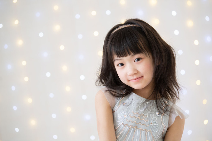 Happy little asian girl in photography studio looking into the camera with a floating light orb backdrop behind her