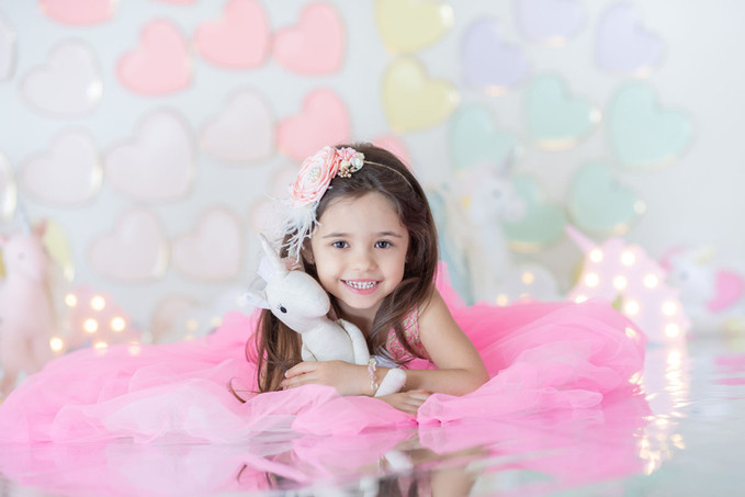 Little girl in a pink dress lying down and smiling into the camera while holding a unicorn plush toy