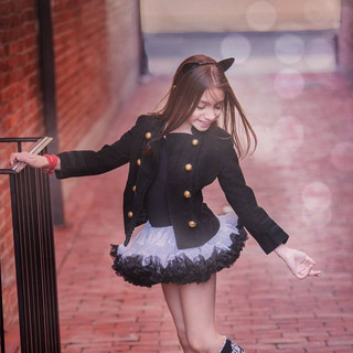 Kids photoshoot of a little girl in a black and white tutu standing in a brick alleyway