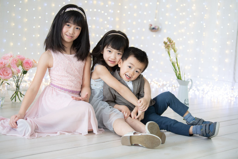 Family portrait of three asian siblings sitting next to each other inside a child photography studio