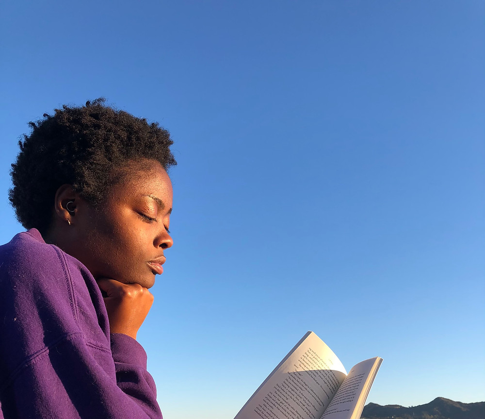 Black woman with short black afro, wearing purple sweater holds a book in one hand and resting her chin on the other. She's turned to profile and the background behind her is the blue sky.