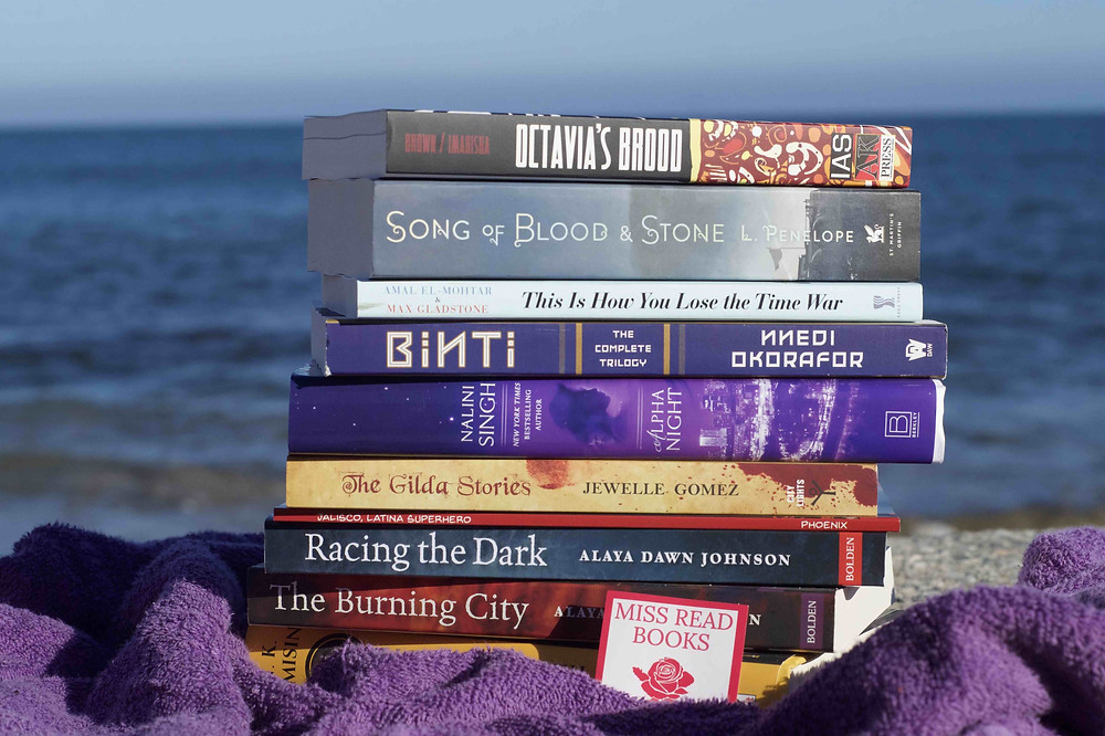"""Stack of diverse sci-fi/fantasy books written by women sitting on a royal purple towel on the sand. Behind the stacks of book, the blue ocean can be seen just slightly out of focus. There's a small pink sticker in front of the stack of books on the towel reading 'MISS READ BOOKS'. Books pictured include: """"Octavia's Brood"""", """"Song of Blood & Stone"""", """"Binti: The Complete Trilogy"""", """"Alpha Night"""", """"The Gilda Stories"""", """"Racing the Dark"""", """"Jalisco"""", """"Racing the Dark"""", """"The Burning City""""."""