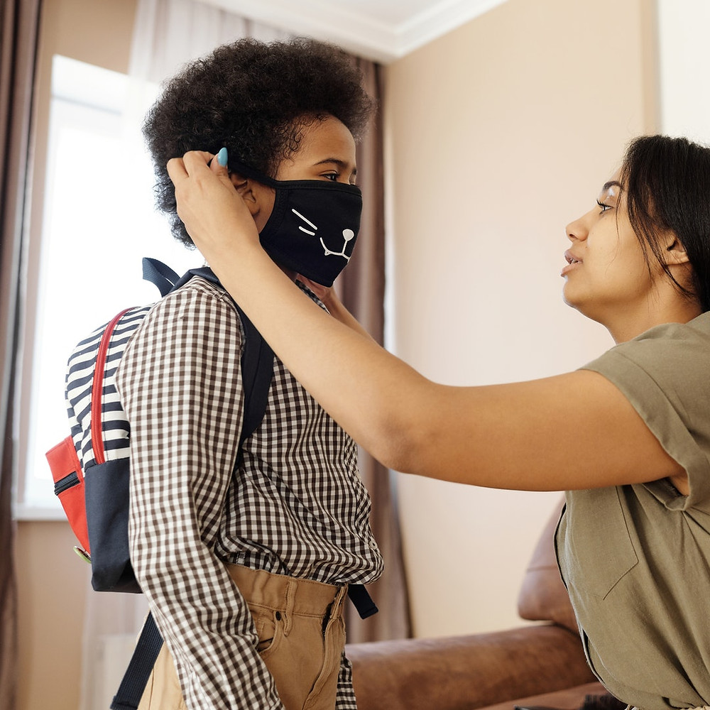 black mom puts face mask on son with backpack