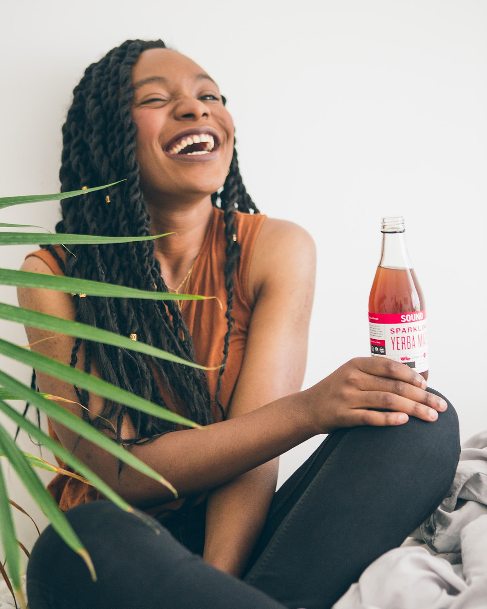 young black woman laughing with a healthy beverage
