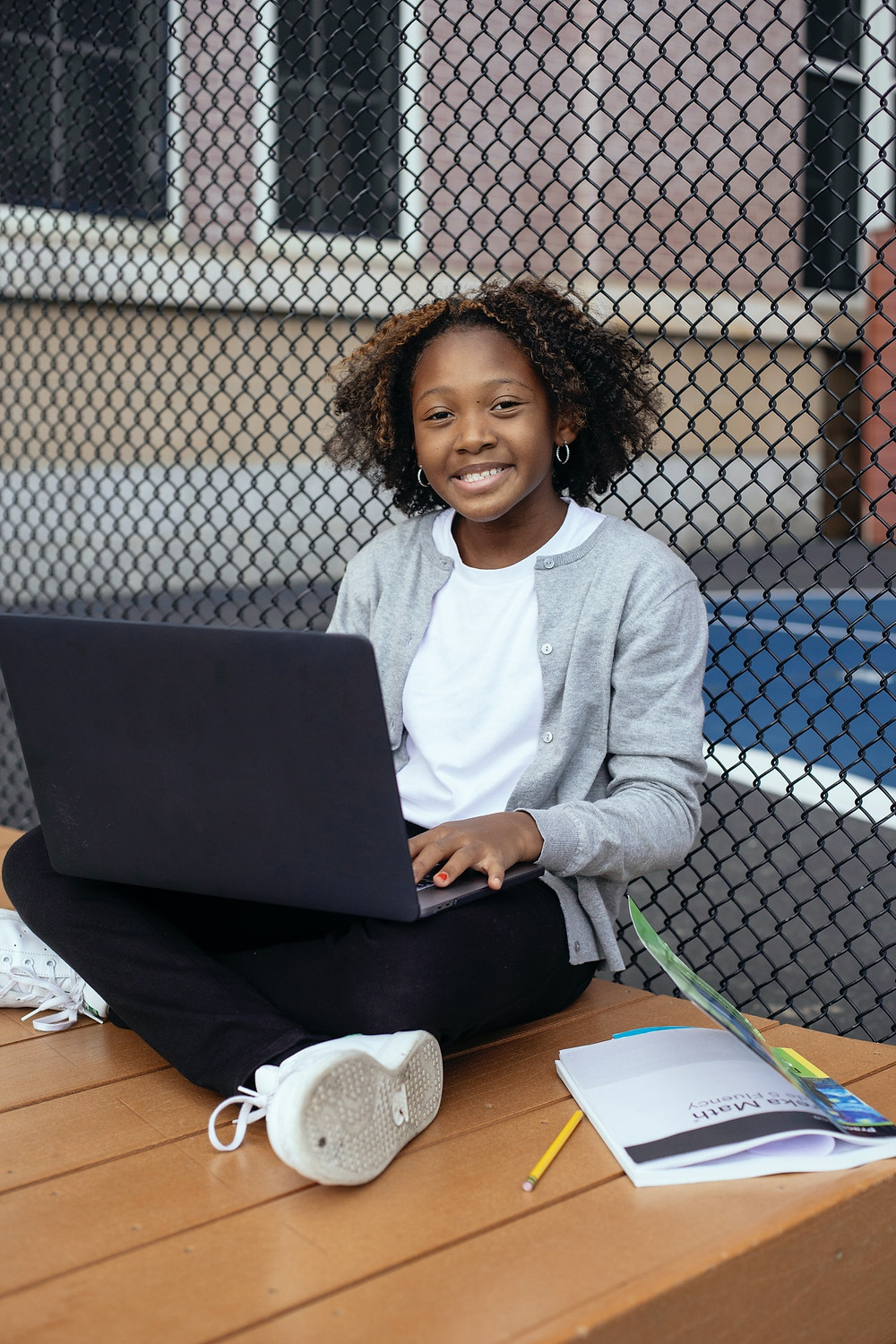 black child smiling with laptop and school workbook