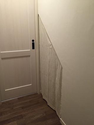 階段下の物入れに斜め型の目隠しカーテン取り付け