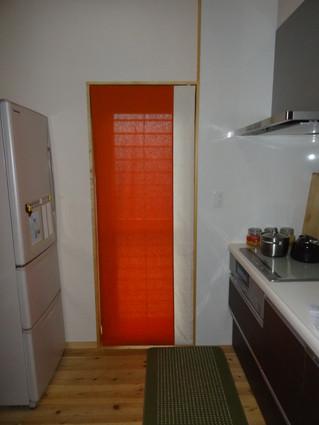 キッチンにオレンジとオフホワイトのツートンシェードを取り付け