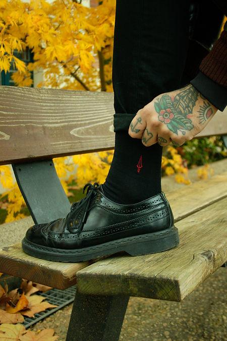 chaussettes noires recyclées Jermaine Toulouse. Ces chaussettes sont fabriquées en France. Tatouages colorés.