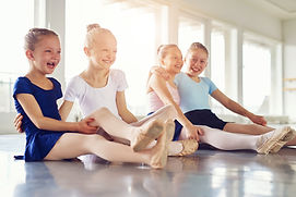 Cheerful young ballerinas smiling and em