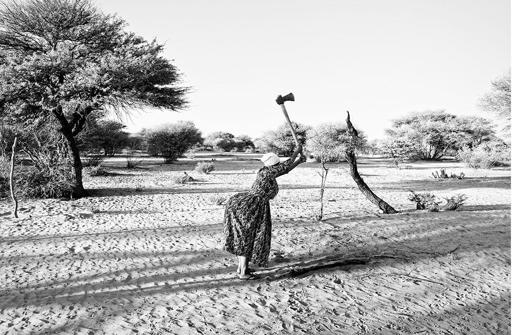 Margaret Courtney-Clarke | Maria Bessa !Gubi chops wood behind her shack at SAA TA KO, Corridor 17, Namibia | 2019 | Piezography Print on Hahnemühle Baryta Paper | 59 x 84 cm | Edition of 6 + 2AP