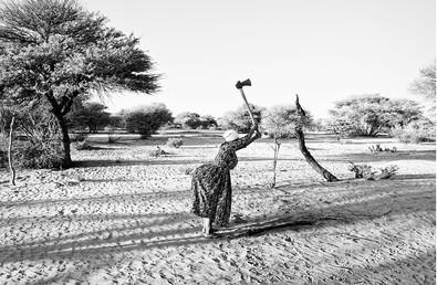 Margaret Courtney-Clarke | Maria Bessa !Gubi chops wood behind her shack at SAA TA KO, Corridor 17, Namibia | 2019 | Piezography Print on Hahnemühle Baryta Paper | 59 x 84 cm | Edition of 6 + 2 AP
