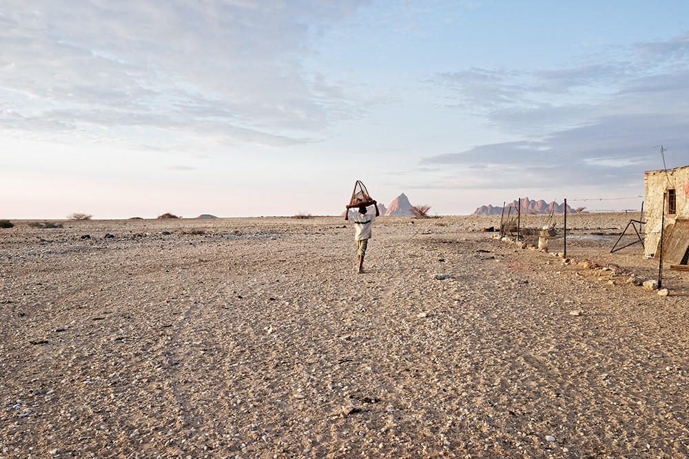 Margaret Courtney-Clarke | Liam !Uri-Khob carries a cage of baby chickens home for the night, Black Ranch, Pos #3, Erongo Region, 9 January 2015 | 2015 | Giclée Print on Hahnemühle Photo Rag Paper | 32 x 48 cm | Edition of 6 + 2 AP