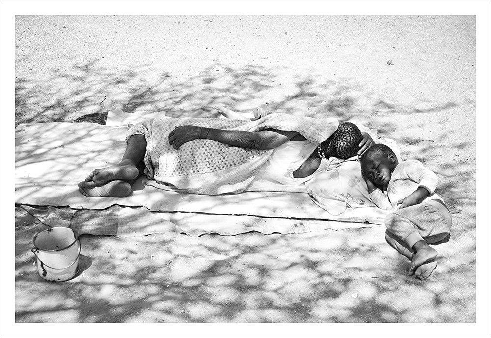 Margaret Courtney-Clarke | !Uoa !Ga-ǀham (Martha Gathone, according to her official identity document) (b. 1958) and her grandson take a nap under the shade of a tree | 2019 | Giclée Print on Photo Rag Baryta Paper | 59 x 84 cm