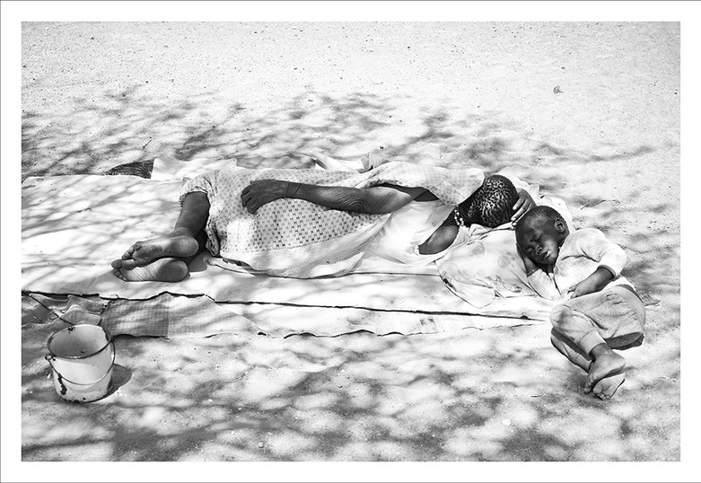 Margaret Courtney-Clarke   !Uoa !Ga-ǀham (Martha Gathone, according to her official identity document) (b. 1958) and her grandson take a nap under the shade of a tree   2019   Giclée Print on Photo Rag Baryta Paper   59 x 84 cm   Edition of 6