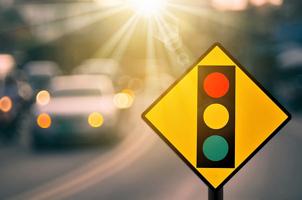 Traffic light warning sign on blur traffic road with colorful bokeh light abstract backgro