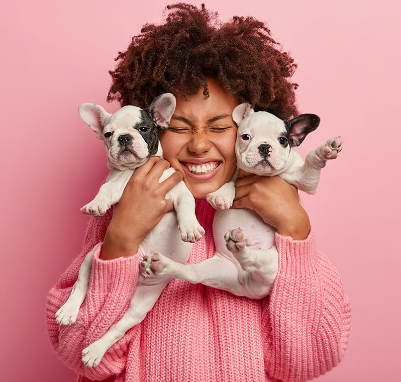 woman smiling and holding two puppies