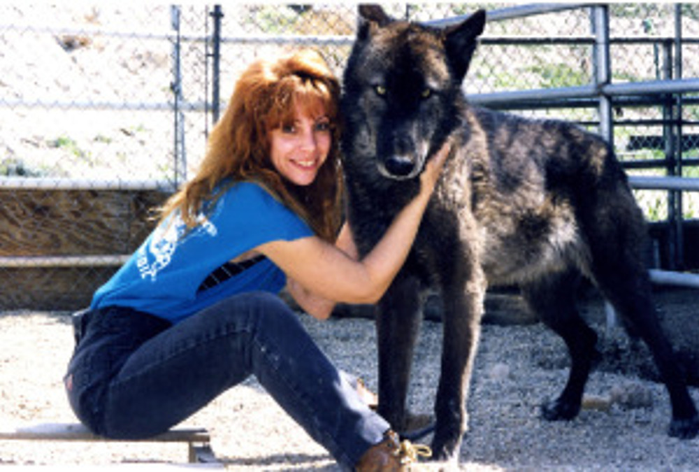 redhead woman sitting with arms around face of large black wolf
