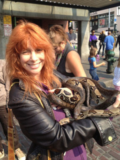 redheaded woman holding snakes