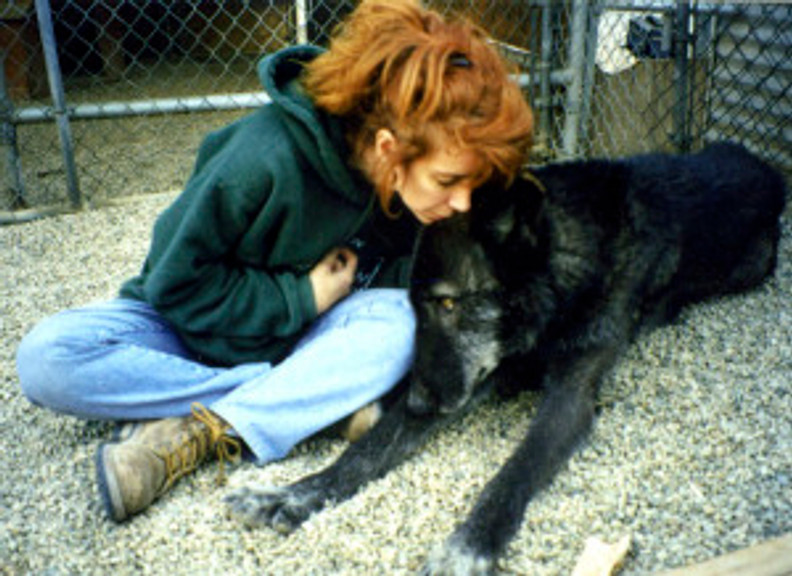 redheaded woman sits on floor with black wolf