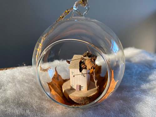 Glass Bauble With Little Wooden House On Real Leaf