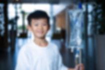 Smiling boy patient holding intravenous