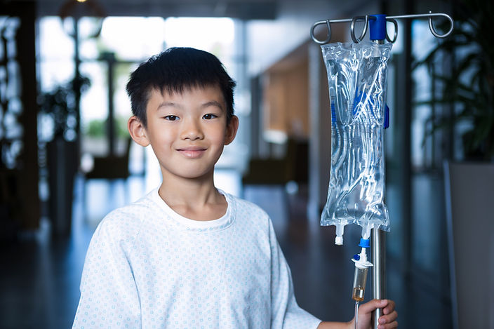 Smiling boy patient holding intravenous